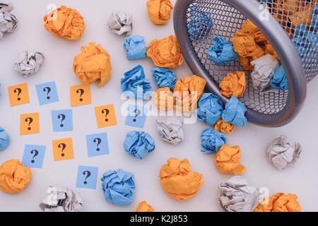 Bunte zerknittertes Papier Kugeln und Fragezeichen Rollen aus einem Mülleimer. Idee, Konzept. - Stockfoto