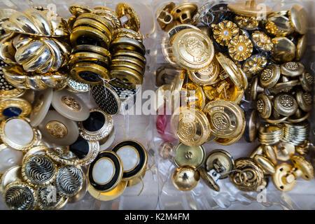 Nahaufnahme einer Sammlung von Gold, Silber und Metall antik vintage Tasten mit verschiedenen Mustern in Kunststoffbehältern - Stockfoto