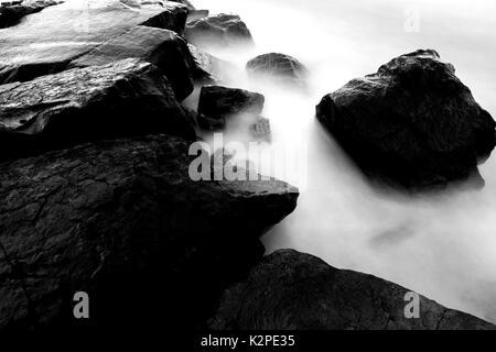 Schwarze und weiße lange Belichtung das Wasser und die Steine Hintergrund in kühlen Farben - Stockfoto