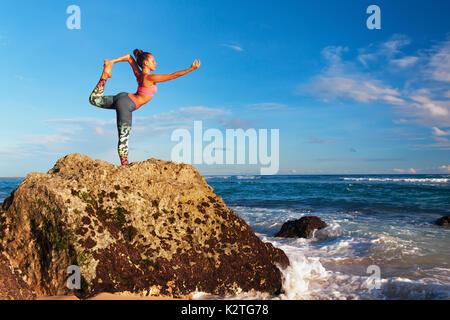 Meditation über Sonnenuntergang Himmel Hintergrund. Junge aktive Frau stand in Yoga pose am Strand Rock passen und - Stockfoto