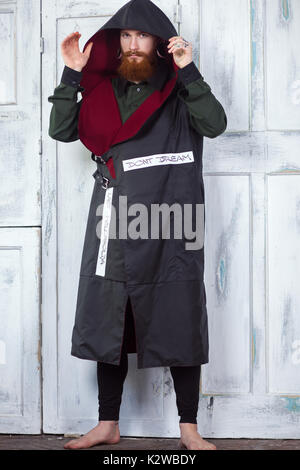 Eine kreative, ungewöhnliche rothaarigen Mann in Designer Kleidung und Tunnel in seinen Ohren, im Studio posing - Stockfoto
