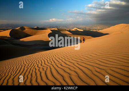 Runner auf Sanddünen in der Wüste in der Nähe von Huacachina Oasis, Ica, Peru, Südamerika - Stockfoto