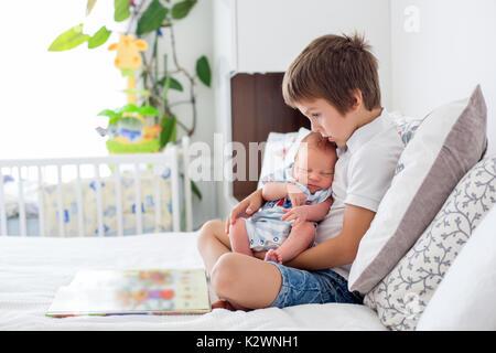 Süße Vorschule Junge, lesen ein Buch zu seinen neugeborenen Bruder, sitzen auf dem Bett im Schlafzimmer, Kindheit Konzept