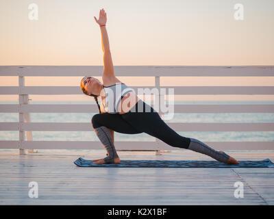 Junge kaukasier Frau Yoga Asana in der Natur auf einem Balkon aus Holz oder Brücke mit Blick auf das Meer. Frau - Stockfoto