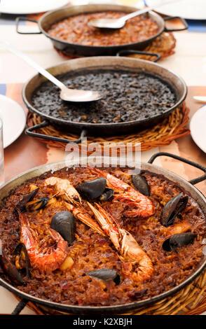 """Nahaufnahme von einigen paelleras, die Paella Pfanne, mit einem typisch spanische Paella, eine """"arroz negro oder - Stockfoto"""