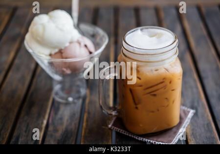Eiskaffee mit Eis auf Holztisch, selektiver Fokus auf Kaffee Tasse, Sommer Dessert - Stockfoto