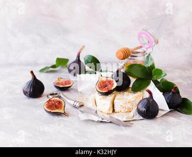 Käse, Feigen und Honig auf weißem Marmortisch, selektiven Fokus - Stockfoto