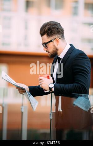 Schöne bärtige Geschäftsmann im klassischen Anzug ist Kaffee trinken und eine Zeitung, während er auf dem Balkon - Stockfoto