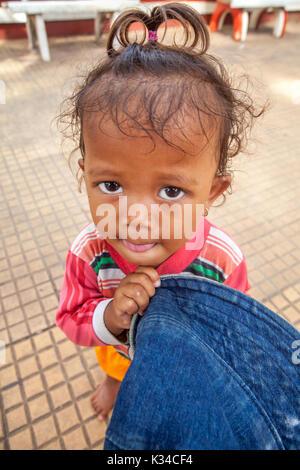 Eine nette junge Kind mit einem blauen Hut und Flehen um Augen bittet auf einem Bürgersteig in Siem Reap, Kambodscha. - Stockfoto