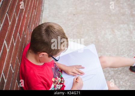 Ein Junge Bücher unten an einer Schule Buch, während seine Hausaufgaben machen und lehnte sich an einer Schule. - Stockfoto
