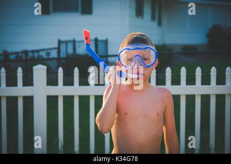 Ein Junge trägt eine scuba Maske in einem Hinterhof im Sommer. - Stockfoto