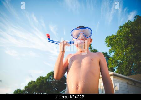 Ein Junge trägt eine scuba Maske gegen einen blauen Himmel mit einigen Wolken. - Stockfoto