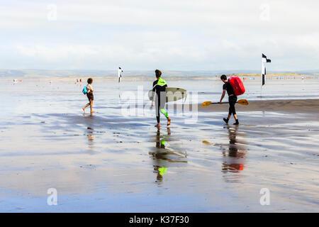Zwei Surfer in Rot, Grün, im Wasser spiegelt, während Sie ihre Surfbretter zum Meer am Sandstrand bei Ebbe in Westward - Stockfoto