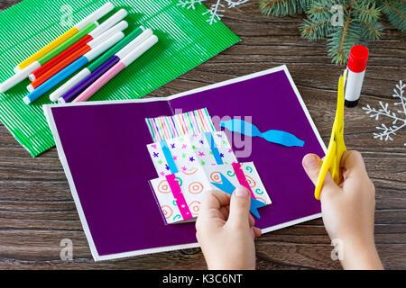 Ein Kind schneidet Details einer Geburtstagskarte mit Weihnachtsgeschenke. mit eigenen Händen gemacht. Kunst für - Stockfoto