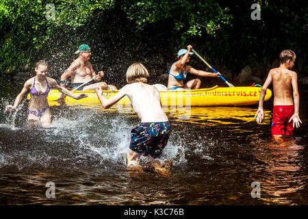 Jugendliche Spritzwasser an einander in den Fluss Otava, vorbei um Senioren in ein Kanu, Tschechische Republik - Stockfoto