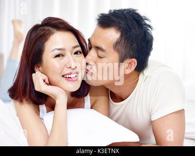 Lieben asiatischen Paar liegen auf der Vorderseite und Küssen im Bett. - Stockfoto