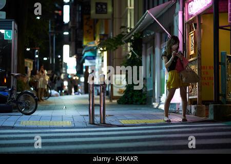 Junge Frau, die an einem Zebras reifen und an Ihrem Mobiltelefon nachts, Tokio, Japan - Stockfoto