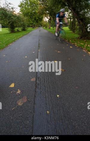 Ein Radfahrer Zyklen durch eine London Park - Stockfoto