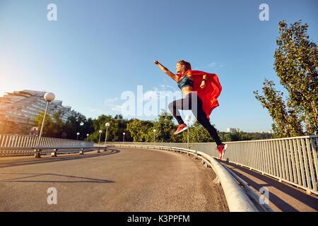 Ein Mädchen Läufer in einem Superhelden Kostüm springt auf der Straße. - Stockfoto