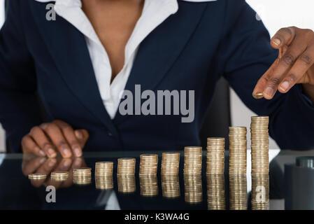 Nahaufnahme einer Geschäftsfrau, die Stapel von Münzen - Stockfoto
