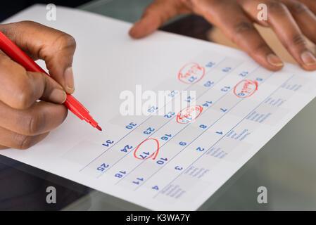 Person Kreisen wichtige Datum im Kalender mit roter Markierung Stockfoto