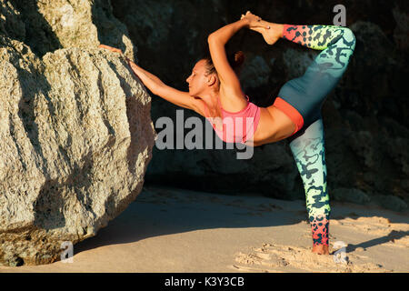 Meditation über rock Hintergrund. Junge aktive Frau stand in Yoga pose am Strand Felsen, Stretching fit und Gesundheit - Stockfoto