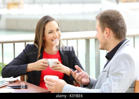 Zwei glückliche Führungskräfte sprechen während der Kaffeepause sitzen in einer Bar - Stockfoto