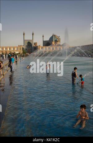 Kinder spielen int er öffentliche Brunnen und Pool in Naqsh-e Jahan Square. Imam Square, Isfahan, Iran - Stockfoto