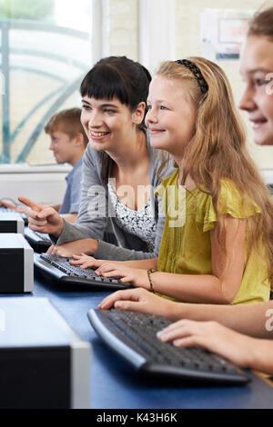 Weibliche Grundschule Schüler im Informatikunterricht mit Lehrer