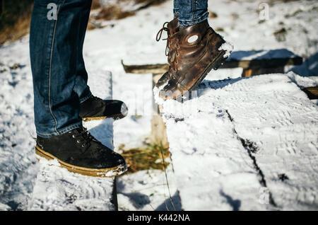Die junge Frau stand vor dem Freund Zehenspitzen. Blick auf die Beine der ein paar in der Liebe. Ein Datum im Winter - Stockfoto