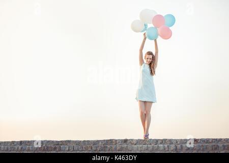 Schöne Frau mit fliegenden bunten Ballons - Stockfoto