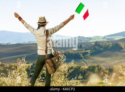 Entdecken Sie magische Ausblicke auf die Toskana. Hinter der jungen Frau Wanderer mit Tasche auf der Toskana Wanderung - Stockfoto