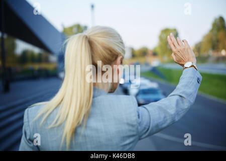 Portrait von unkenntlich Geschäftsfrau, die versuchen, Taxi zu erreichen. - Stockfoto
