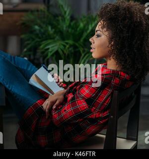 Profil Portrait von nachdenkliche junge Frau mit Notizbuch mit Stift und Wegsehen - Stockfoto
