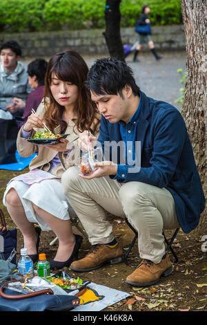Ein japanisches Paar bei einem Picknick in Ueno Park Onshi, Taito, Tokio, Japan, Asien. - Stockfoto