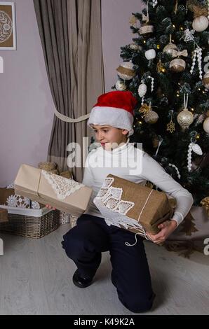 Lächelnde junge tragen weiße Pullover und Santa red hat mit aufgewickelte Weihnachtsgeschenke in der Nähe von geschmückten - Stockfoto