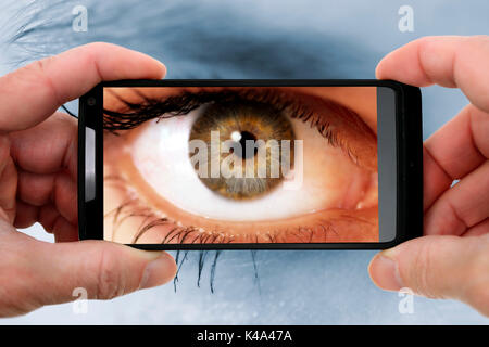 Womans Auge in einem Handy, Gawker - Stockfoto