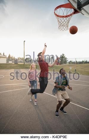 Teenage Freunde Basketball spielen auf Baskettballplatz draußen - Stockfoto