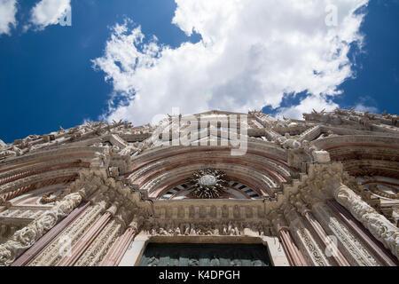 Die Fassade der Kathedrale von Siena vor dem Hintergrund des blauen Himmels und flauschigen weissen Wolken, Siena - Stockfoto