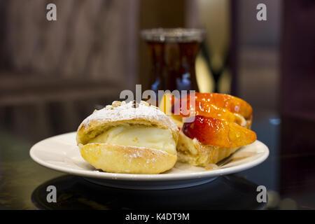 Brötchen mit Vanillepudding und Puderzucker. peach Pie in der Glasur. - Stockfoto