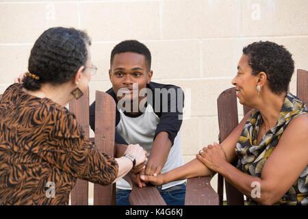 Closeup Portrait, schönen jungen Mann mit Gespräch mit Familie hinsetzen, isoliert im freien Hintergrund - Stockfoto