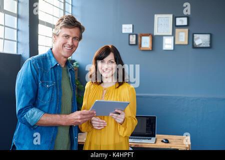 Porträt von zwei selbstbewussten jungen Arbeitskollegen zusammen arbeiten, während in einem modernen Büro stehend - Stockfoto
