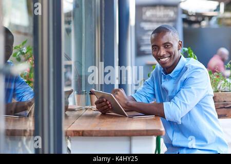Porträt einer jungen afrikanischen Mann lächelnd, während außerhalb an einem Zähler einer Sidewalk Cafe online arbeiten - Stockfoto