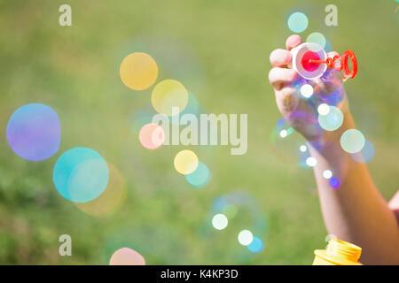Girl's Hand mit einem Bubble Maker und bläst Seifenblasen, gegen die unscharfe Gras Hintergrund Stockfoto