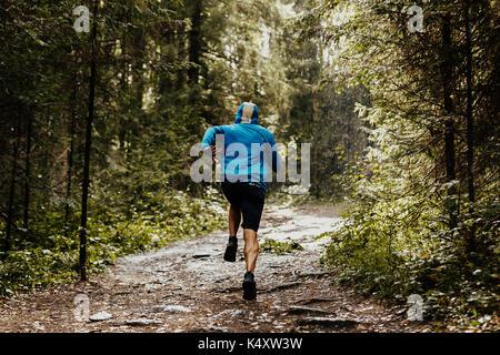Zurück männliche Läufer Athlet in der Motorhaube läuft Wald - Stockfoto