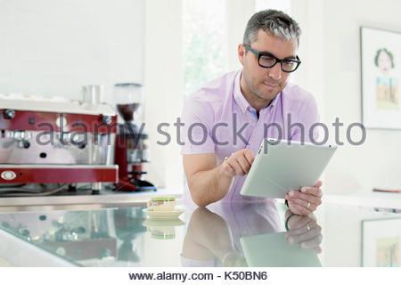 Junge weiße Mann auf seinem ipad in der Küche arbeiten - Stockfoto