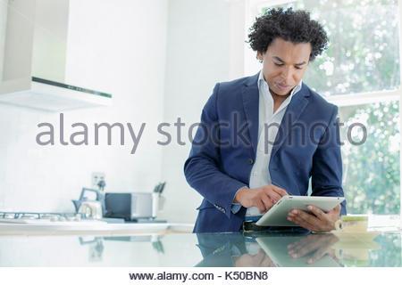 Junge afrikanische Mann auf seinem iPad in der Küche arbeiten - Stockfoto