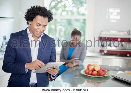 Junge afrikanische Mann bei der Arbeit auf seinem iPad in der Küche, und Kollege auf der Suche - Stockfoto