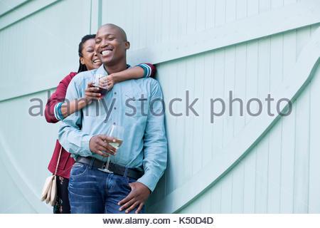 Glückliches Paar stehend durch eine hölzerne Tür - Stockfoto