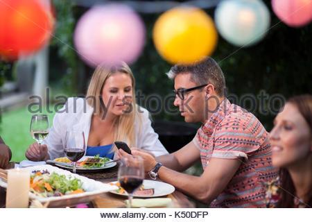 Zwei Freunde, die an einem Telefon am Tisch - Stockfoto